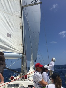 Spinnaker on the SV Spirit of Juno is being managed by the man to the right of the photo, wearing a cream-colored hat