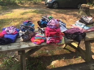 A few days of clean laundry, folded on a picnic table.