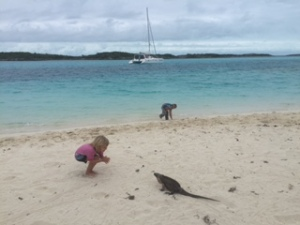 Karen (4) with an Bahamian Rock Iguana. Henry (4) and our catamaran, SV Aphrodite, in the background.